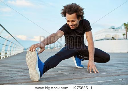 Fitness and motivation. Joyful and smiling dark-skinned athlete stretching on pier in the morning. Sporty Afro-American male with bushy hair warming up his legs before running exercise outdoors.