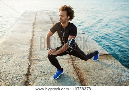 Young male dark-skinned runner with beautiful fit body warming-up his muscles before strength training cardio workout. Man athlete in sportswear stretching legs with lunge hamstring stretch exercise on pier.