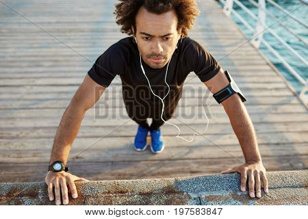 Dark-skinned man runner in black sportswear standing in plank position warming up before cardio workout on the pier in the morning. Afro-american male athlete wearing black sport suite and blue sneakers, in white aerphones using music app during warming u