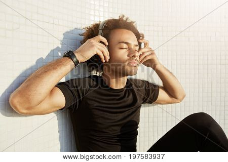 Peaceful dark-skinned sportsman with bushy hairstyle and closed eyes wearing big headphones enjoying music. Portrait of handsome muscular Afro-American male listening music, putting his hands on headphones on a white background in black sport wear.