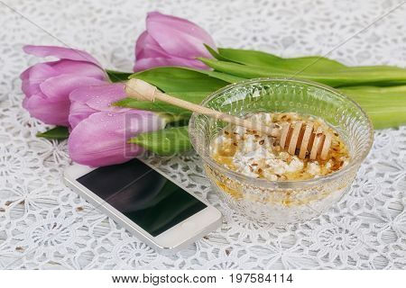 Healthy breakfast. Cup of karkadeh red tea cottage cheese plus oat flakes linseed and honey on the table with purple tulips and smartphone