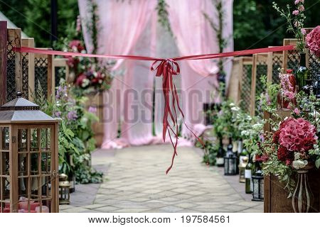 Beautiful wedding ceremony outdoors. Decorated chairs and wedding aisle with an awesome bow. Rustic style.