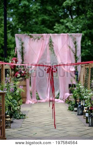 Beautiful wedding ceremony outdoors. Decorated chairs and wedding aisle with an awsome bow. Wedding arch made of cloth and white and pink flowers on a green natural background. Rustic style.