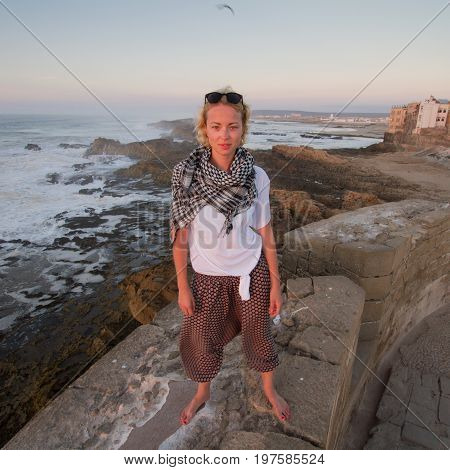 Female traveler standing barefooted on city fortress wall of Essaouira, Morocco. Travel lifestyle adventure concept. Active vacations. Solo female world traveler. Strong indepandant woman.