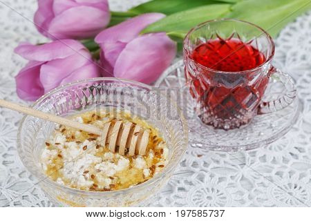 Healthy breakfast. Cup of karkadeh red tea cottage cheese plus oat flakes linseed and honey on the table with purple tulips