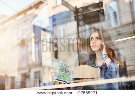 Female tourist holding a map talking on phone sitting in cafe lost. Pursuing her passion to travel. Shot through glass.