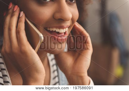 Pleasant conversation. Close-up of joyful mulatto girl is having communication using smartphone and expressing happiness while touching her face