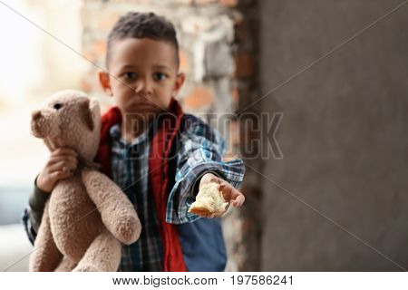 Cute little boy with piece of bread in abandoned building. Poverty concept