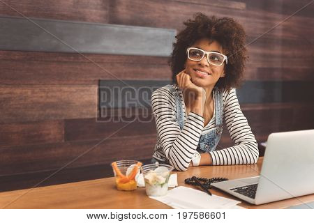 Dreamy look. Charming girl in glasses is leaning on table and touching her chin while looking aside wistfully. She is having vegetarian lunch. Copy space in the left side