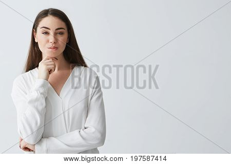 Young beautiful playful businesswoman with cunning tricky glance smiling looking at camera over white background. Copy space.
