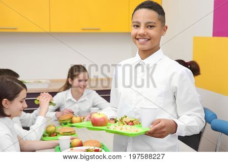 Cute boy holding tray with delicious food in school canteen