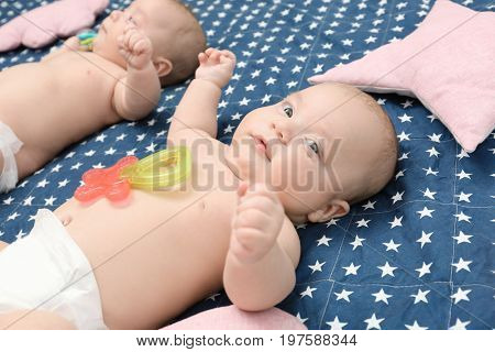 Beautiful baby twins lying with rattles on bed sheet