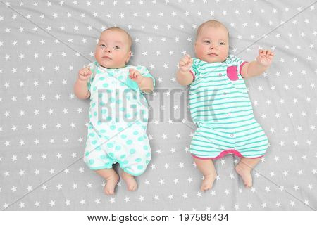 Beautiful baby twins lying together on bed sheet
