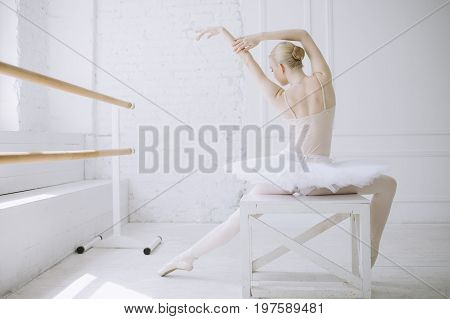 Slim and well-built ballerina is sitting backwards on the chair near the window in the big white classroom. Girl is stretching and looking down to the floor preparing for the lesson.