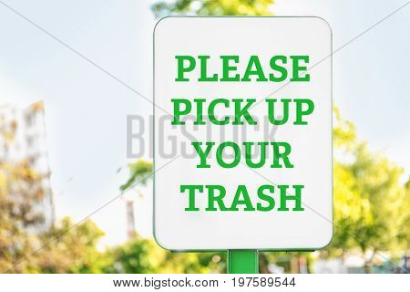Signboard with text PLEASE PICK UP YOUR TRASH outdoors