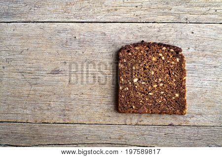 Slice of whole grain brown bread on wooden table.