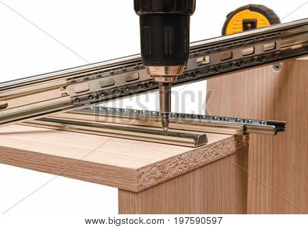 Assembling furniture from chipboard, using a cordless screwdriver, close up.