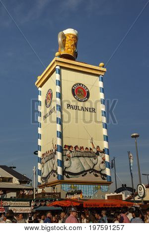 Munich, Germany - September 24, 2016: Roof of the Paulaner tower with the famous beer stein and unidentified people walking by
