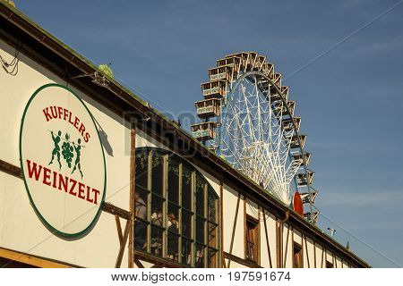 Munich, Germany - September 24, 2016: Ferris wheel on the fairground of the Octoberfest in Munich with the Weinzelt building in front