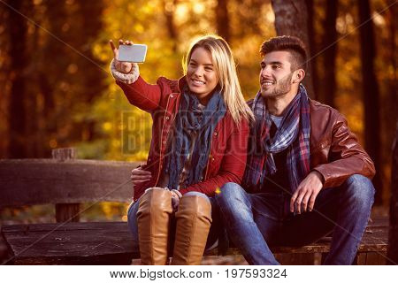 love in the autumn park- couple in the park taking selfie