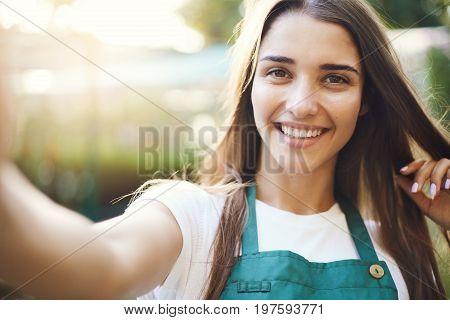 Portrait of beautiful woman gardener taking a selfie in her own garden supplies shop