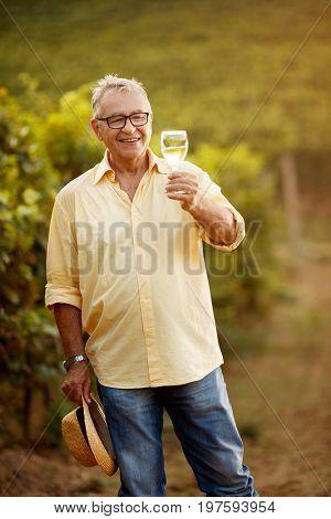 Happy winemaker tasting white wine in vineyard