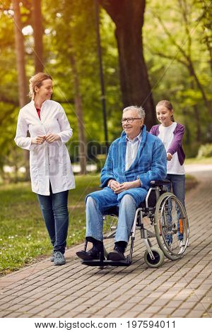 portrait of elderly man on wheelchair with caregiver nurse and granddaughter outdoor