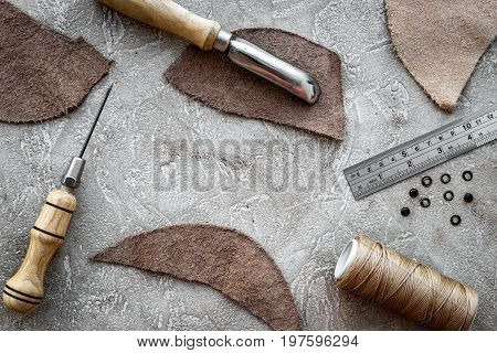 Leather worker workplace. Tanner's tools on grey stone background top view.