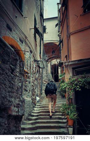Hiker in alley in Riomaggiore in Cinque Terre, Italy.
