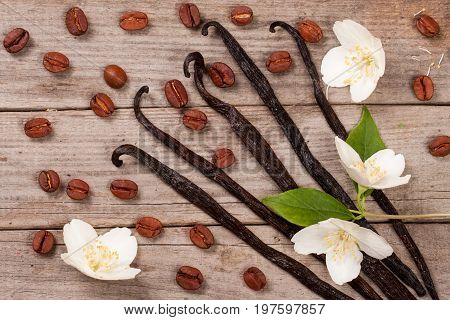 Vanilla sticks with coffee beans and flower on a old wooden background.