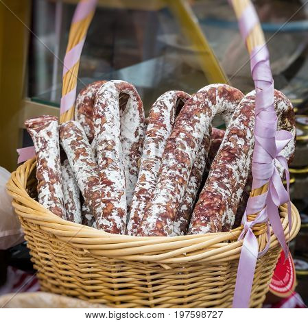 Gastronomic products for gourmets, traditional italian salami in wicker basket close-up. Real scene in the market.