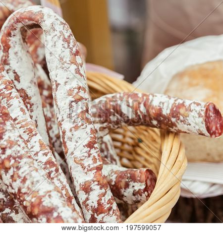 Close-up of traditional italian tasty delicacies in wicker basket, picant organic salami in market. Gastronomic products for gourmets