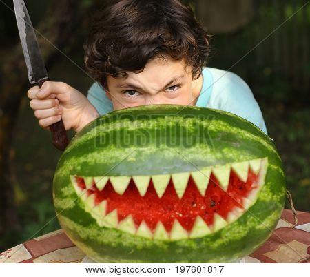teenager boy show monster with cut shark teeth water melong mouth an knife grimasing evil