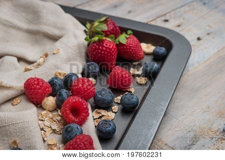 Fresh healthy ingredients for breakfast or smoothie on dark vintage board. Blueberries raspberries and strawberries. Summer and healthy food concept.
