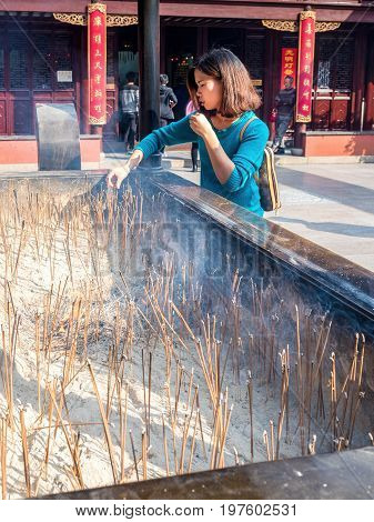 Shanghai, China - Nov 6, 2016: A young lady offering incense at 600-year-old Old City God Temple. The sticks of incenses are placed in a large urn, burning together with lots of others.