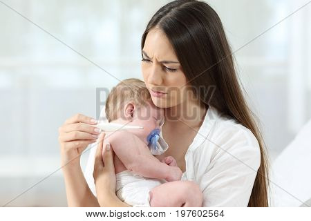 Mother checking thermometer holding her ill baby at home