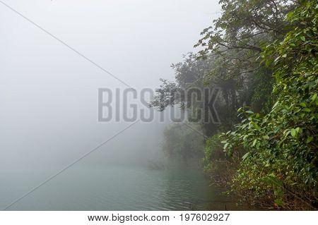Forest at foggy volcano crater lake La Fortuna Costa Rica