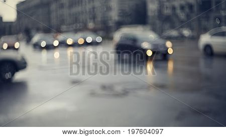 Blurry unfocused background with the city road with cars in twilight after a rain. Out of focus city landscape in twilight after a rain.