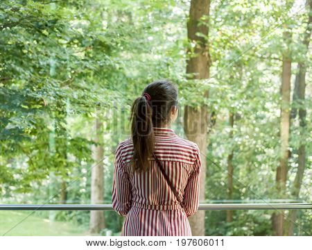 woman looking into the window on sunny green forest