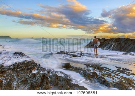 Surfer standing on rocks watching the ocean waves passing with ocean flowing in at Currumbin Rock, Gold Coast.