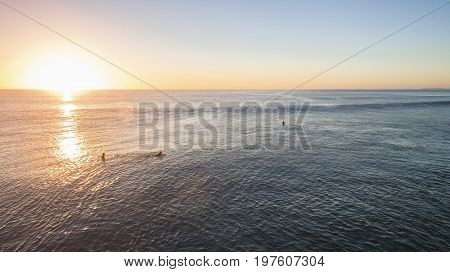 Aerial view of sunrise rising over ocean, with surfers wading in the water.