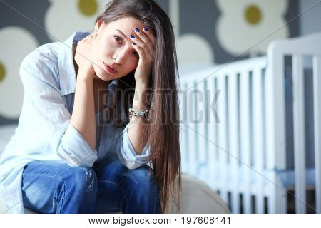 Young tired woman sitting on the bed near children's cot. Young mom.
