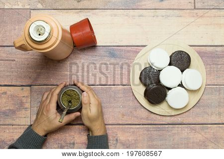 drinking mate with alfajores on the wooden table