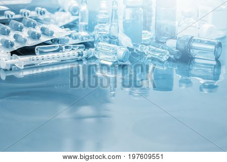Glass Medicine Vials ampule , medicine pill and capsule Syringe on x-ray film over doctor table for background with copy space on front area