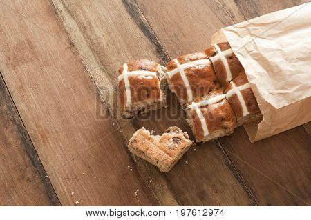 Brown paper packet with fresh hot cross buns from the bakery to celebrate Easter spilling out onto a wooden table with copy space