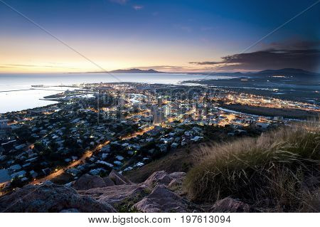 Cityscape of illuminated Townsville and ocean at dusk Australia