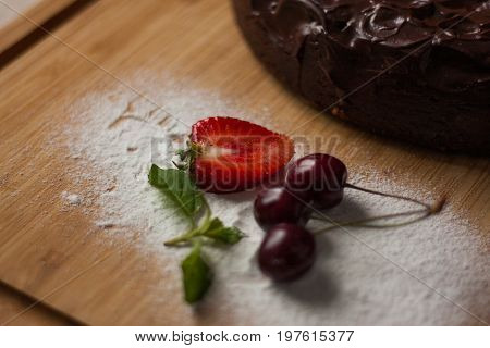 A food photo of delicious chocolat and cocoa dessert lying on wooden background and decorated with strawberry and cherries, ideal for breakfast.