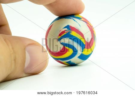 Index Or Pointing Finger Touching Colorful Rubber Marble Ball Isolated On White