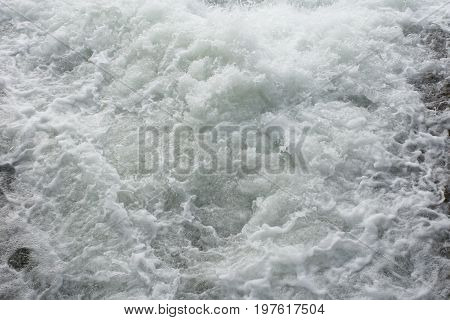 Close up of churning white water in a fast moving river. Photographed from above.