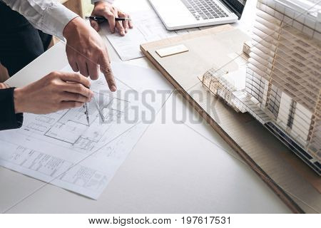 Engineering or Creative architect in construction project Engineers hands working with compasses on construction blueprint building model at a workplace in office Building and architecture concept.